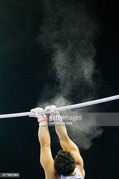 Penn State's Alexis Torres grips the horizontal bar with crossed hands after a release in his routine during the Team and All Around Finals of the...