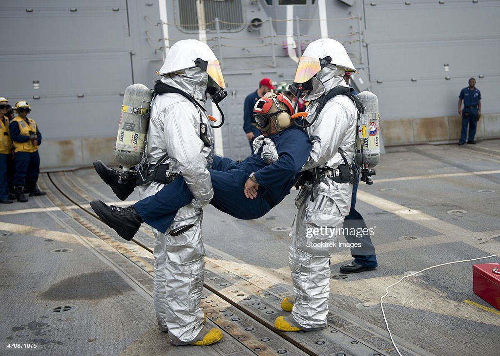 April 22, 2013 - Sailors simulate rescuing a pilot during a crash and salvage drill aboard the guided-missile destroyer USS William P. Lawrence (DDG-110).
