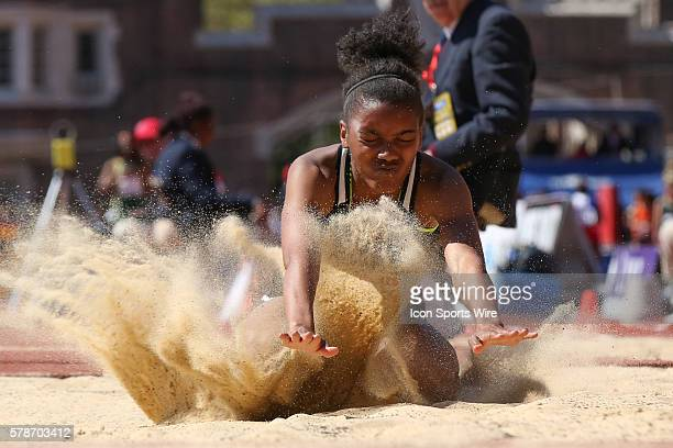Cidae'a Woods from Winslow New Jersey sprays the sand during her landing as she competes in the girls high school long jump competition during the...