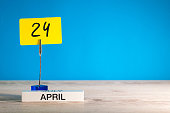 April 24th. Day 24 of april month, calendar on little yellow tag. Spring time. Empty space for text, mockup or template.