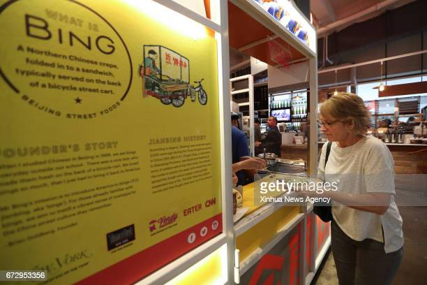 NEW YORK April 25 2017 A customer collects her Jianbing at the kiosk of Mr Bing in UrbanSpace food court in New York the United States April 17 2017...