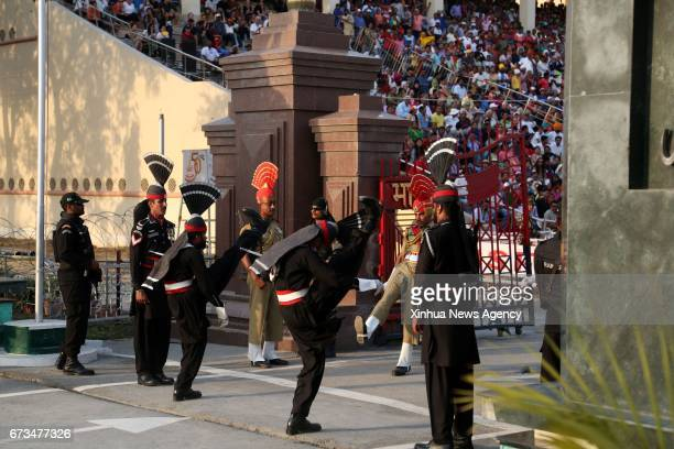 LAHORE April 26 2017 Pakistani soldiers and Indian soldiers perform during a flag lowering ceremony at Wagah border between Pakistan and India in...