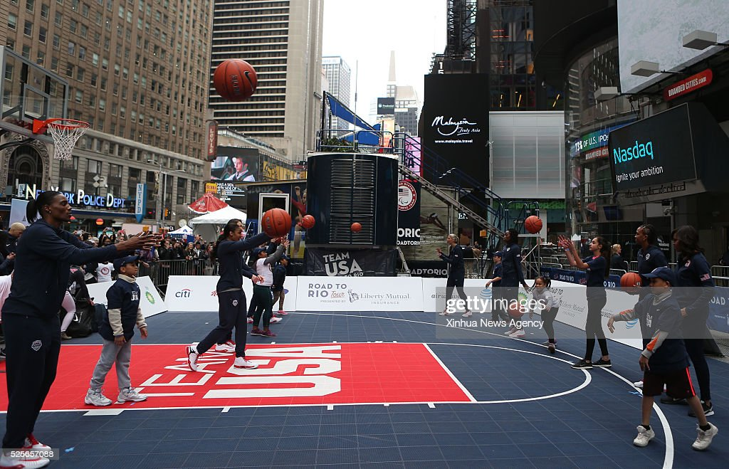 NEW YORK, April 28, 2016 -- Children take part in the basketball demonstration during the Team USA's 'Road to Rio Tour' activity at Times Square in New York, the United States on April 27, 2016. Team USA's 'Road to Rio Tour' was held at Times Square on Wednesday to mark the 100-Day countdown to the 2016 Olympic Games in Rio de Janeiro. More than 70 Olympic and Paralympic athletes participated in the event and shared their spirit and excitement of the Games with fans here.