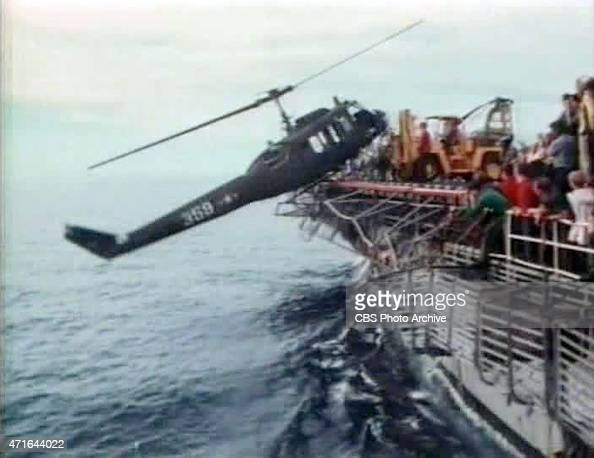 April 29 1975 US Navy personnel of the USS Blue Ridge push a helicopter into the South China Sea off the coast of Vietnam in order to make room for...
