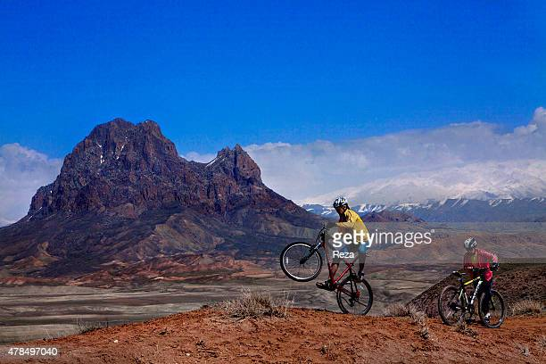 April 4 Ilandagh Mountain Nakhchivan Azerbaijan Azerbaijani men ride mountain bikes on the dry terrain surrounding the Ilandagh Mountain wreathed...