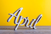 April - carved text of wooden at light yellow background. Second spring month.
