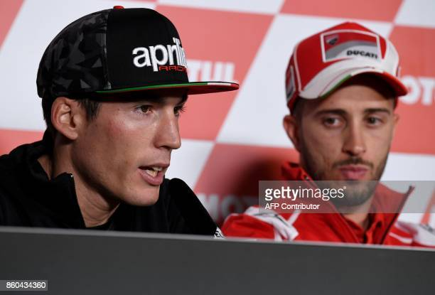 Aprilia rider Aleix Espargaro of Spain answers a question beside Ducati rider Andrea Dovizioso of Italy during a press conference at Twin Ring Motegi...