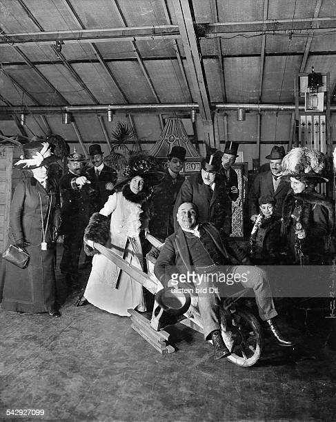 eine Frau schiebt einen Mann in einer Holzschubkarre1910Foto Zander Labisch