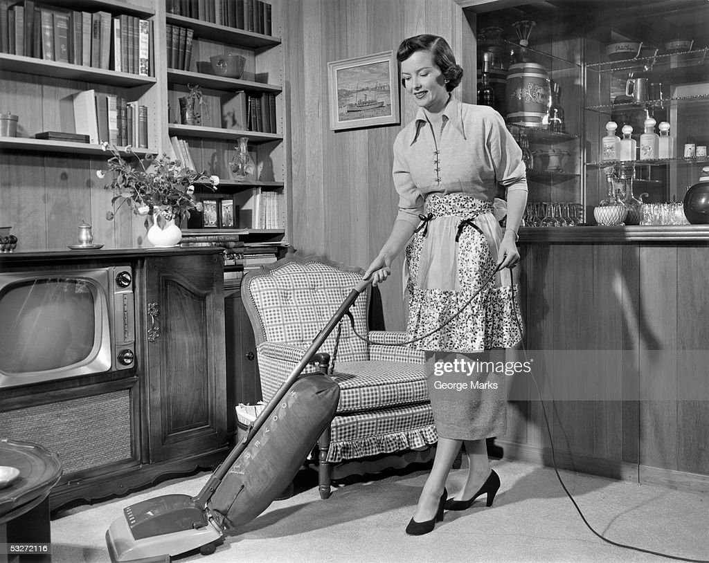 Apron housewife vacuuming den : Stock Photo