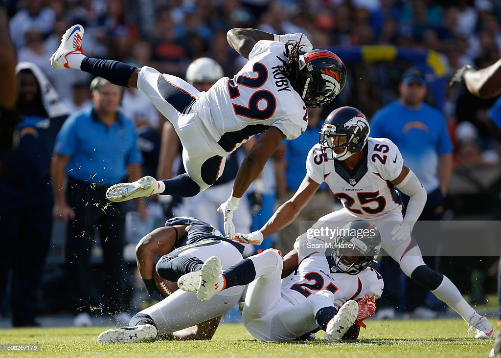 Aqib Talib #21 of the Denver Broncos, Chris Harris #25 of the Denver Broncos, and Bradley Roby #29 of the Denver Broncos tackle Antonio Gates #85 of the San Diego Chargers during the first quarter of a game at Qualcomm Stadium on December 6, 2015 in San Diego, California.