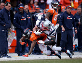 Aqib Talib of the Denver Broncos tackles Rob Gronkowski of the New England Patriots after a first down in the third quarter in the AFC Championship...