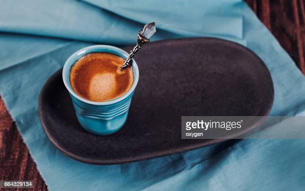 aqua cup with espresso on dark wooden background