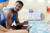 Portrait of handsome African-American fitness coach talking to client in swimming pool, copy space