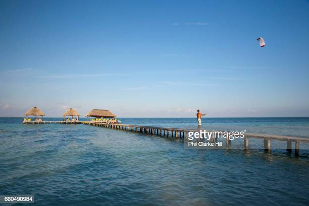Aquamarine ultramarine deep blue waters and beach on Cayo Coco island and resorts with a man flying a kite on a pier / jetee on a private beach in an...