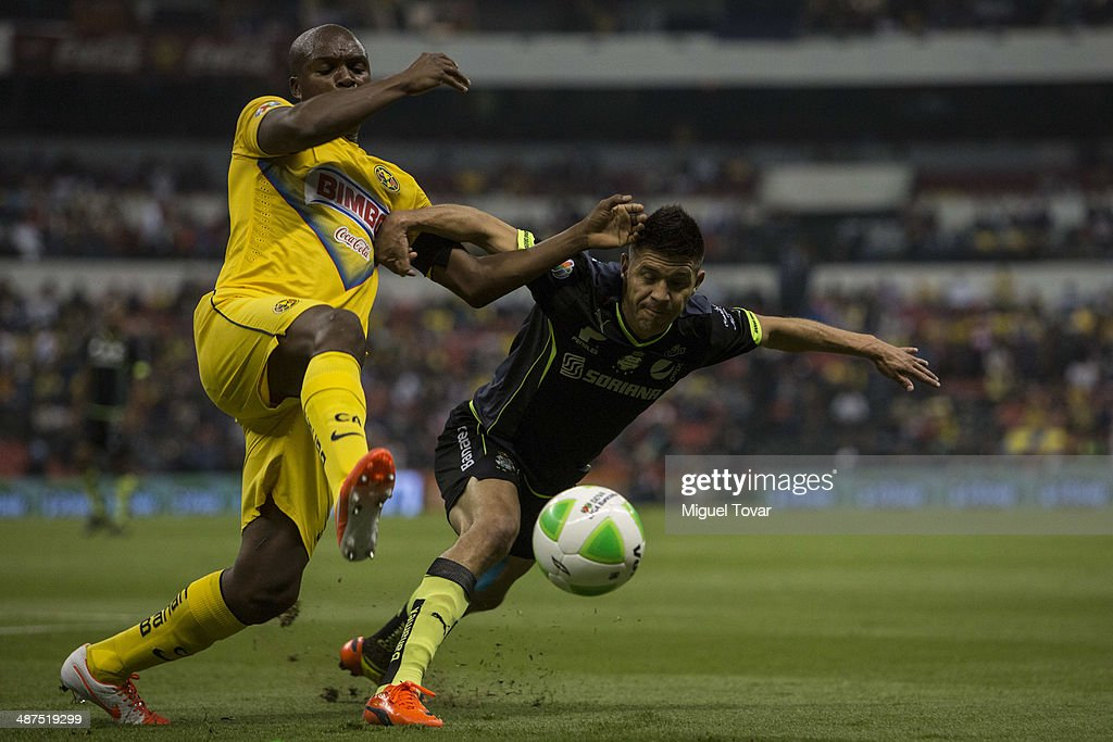 <a gi-track='captionPersonalityLinkClicked' href=/galleries/search?phrase=Aquivaldo+Mosquera&family=editorial&specificpeople=624234 ng-click='$event.stopPropagation()'>Aquivaldo Mosquera</a> of America fights for the ball with <a gi-track='captionPersonalityLinkClicked' href=/galleries/search?phrase=Oribe+Peralta&family=editorial&specificpeople=2496229 ng-click='$event.stopPropagation()'>Oribe Peralta</a> of Santos during the Quarterfinal first leg match between America and Santos Laguna as part of the Clausura 2014 Liga MX Playoffs at Azteca Stadium on April 30, 2014 in Mexico City, Mexico.
