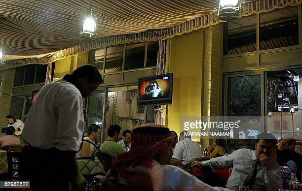 Arab and foriegn clients smoke waterpipes as they watch the Bahraini TV series 'Dhil alYassamin' at a Ramadan tent in Dubai late September 22 2008...