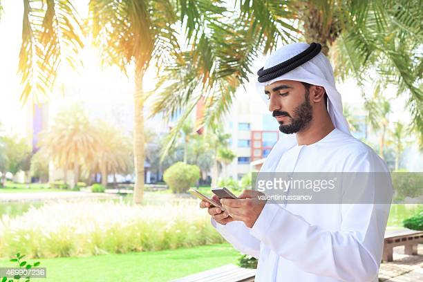Arab bisunessmen texting on the phone