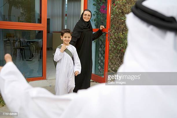 Arab boy leaving school, waving to his father. Dubai, United Arab Emirates