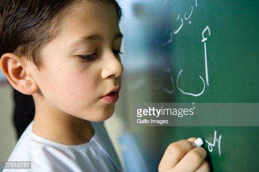 Arab Boy Writing on a Blackboard in a Classroom, side view. Dubai, United Arab Emirates