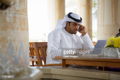 Arab Business Man using Mobile Phone and Computer, sitting on Patio Table in Restaurant. Dubai, United Arab Emirates
