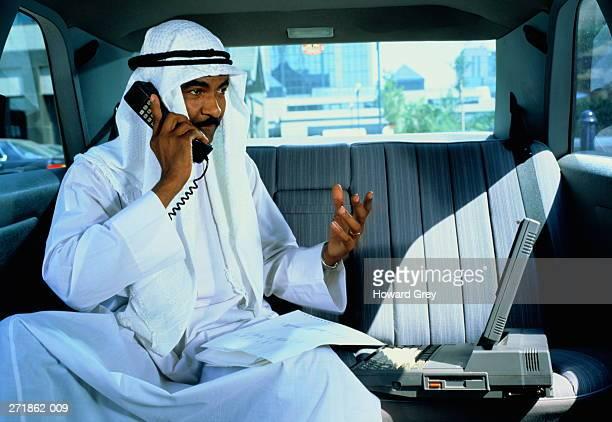 Arab businessman in executive car using phone