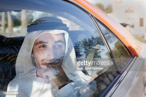 Arab businessman in traditional dress in car