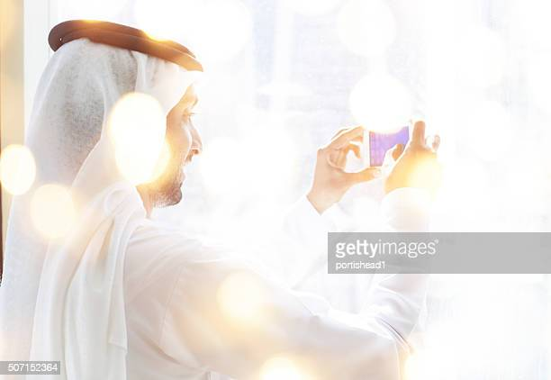 Arab businessman looking through business building window