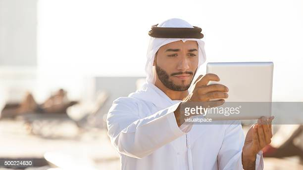 Arab Businessman Using Digital Tablet on a Skyscraper's Rooftop