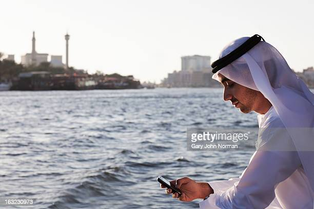 Arab businessman using phone, Dubai Creek