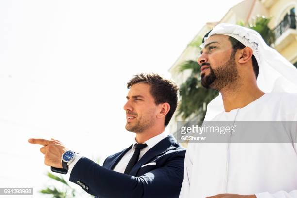 Arab businessman viewing his investments with a foreign business executive
