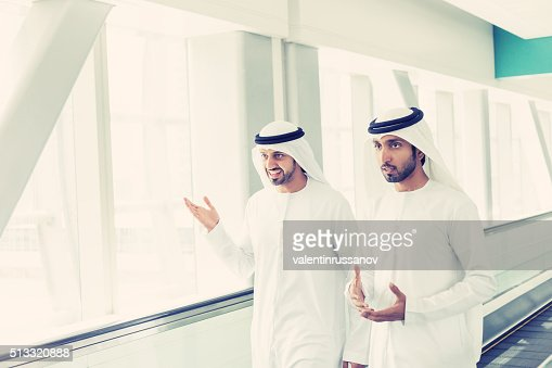 Arab businessmen in traditional clothes at Dubai Subway Station