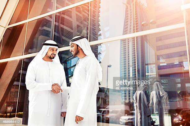 Arab businessmen in traditional clothes in front of Dubai Metro