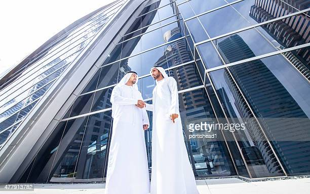 Arab  businessmen in traditional clothes in front of modern building