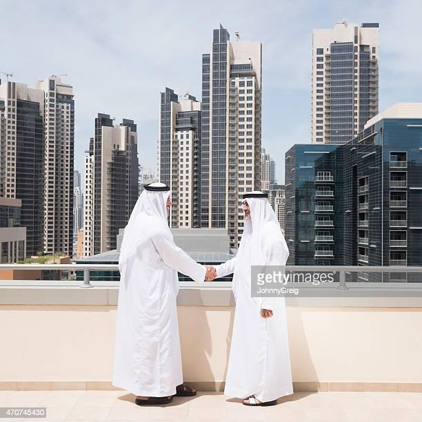 Arab businessmen shaking hands on property deal