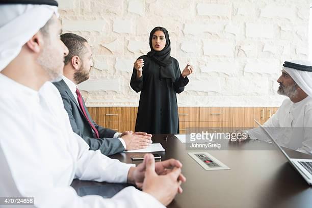Arab empresaria dando presentación a sus compañeros de trabajo en oficina