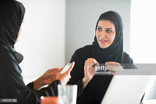 Arab businesswomen in traditional clothes discussing in office
