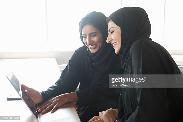Arab businesswomen in traditional clothing using tablet PC