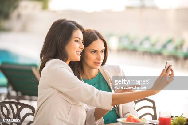 Arab Businesswomen Looking at Cellphone and Having Business Lunch at Hotel