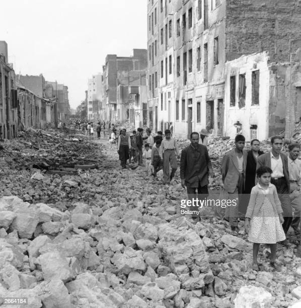Arab civilians walking through the rubble of bombed streets in Egypt during the Suez Crisis