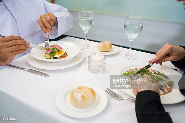 Arab couple eating meal in restaurant, high angle view. United Arab Emirates
