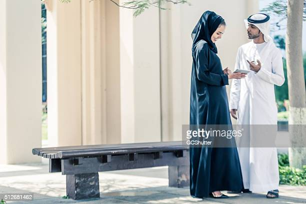 Arab Couple in a Park with their Digital Tablet