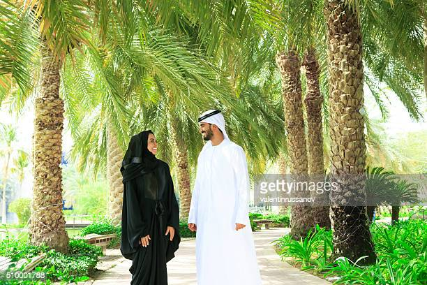 Arab couple walking in the park with palms