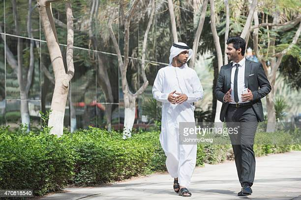 Arab emirati businessman walking and talking with business colle