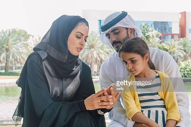 Arab family enjoying smartphone at park