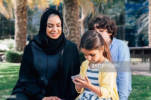 Arab famille appréciant avec son smartphone dans le parc