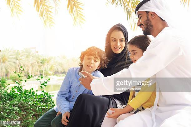 Arab family looking pictures on phone in the park