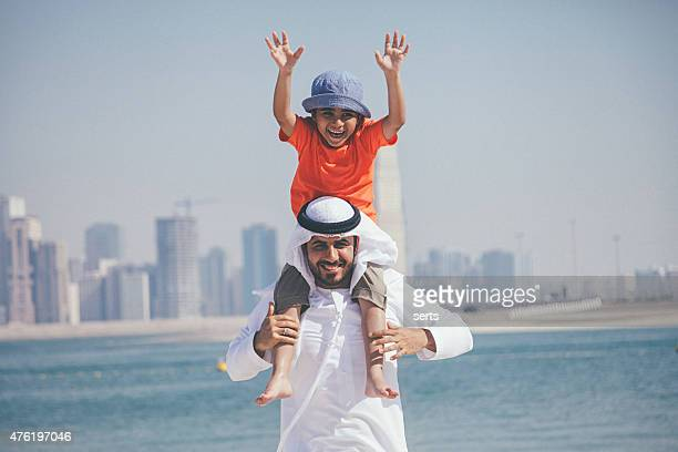 Arab father and son having fun at beach