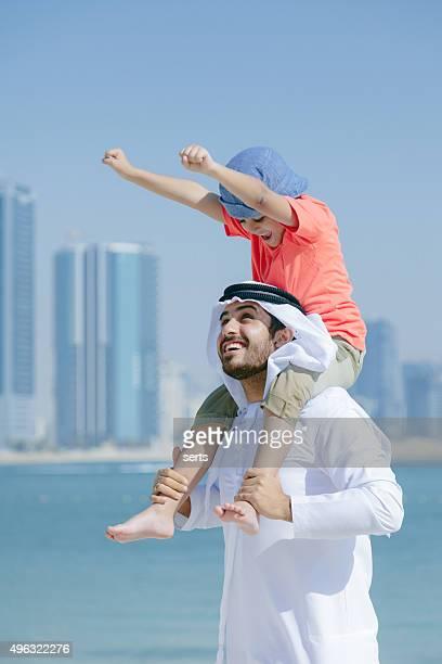 Arab father and son having fun at beach