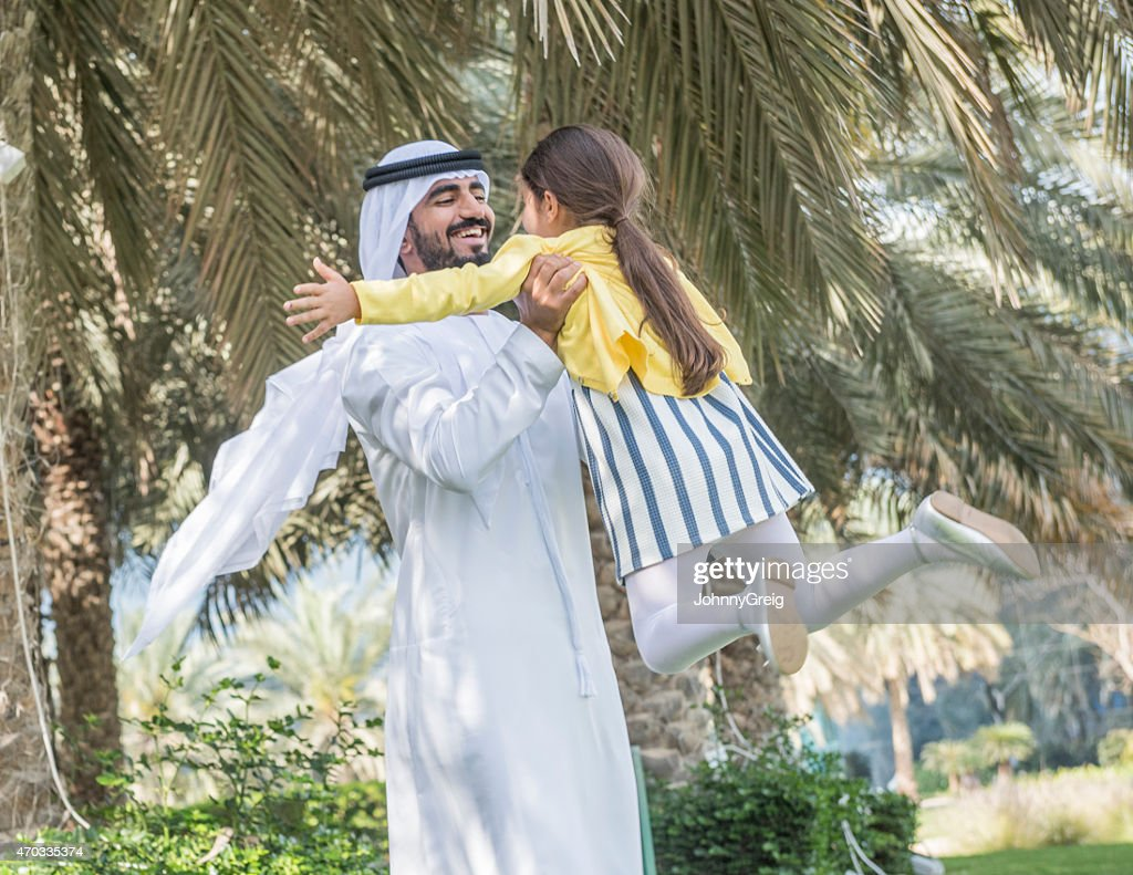 Arab father enjoys swinging his young daughter in his arms