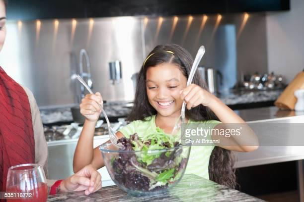 Arab girl mixing salad in bowl.